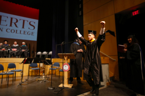 graduate raising hands in triumph