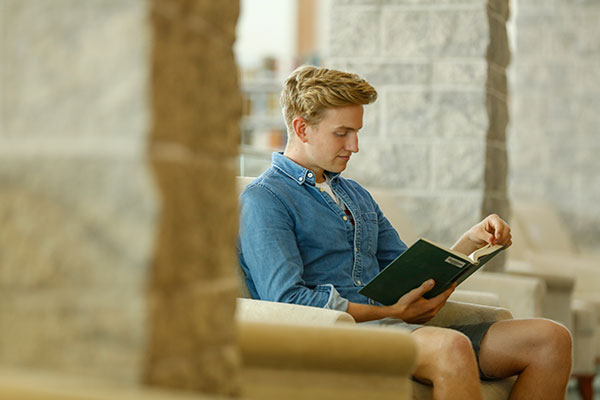 student in Golisano Library at Roberts Wesleyan College
